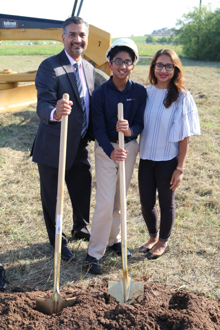 family standing with shovels, groundbreaking